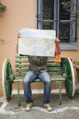 Man on bench reading a map