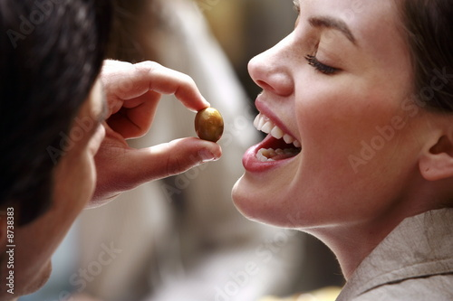 Man feeding woman an olive