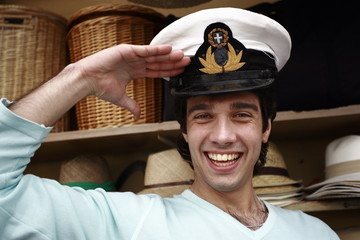 Man trying on naval hat;saluting