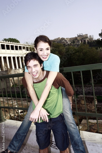 Man giving woman a piggy back ride