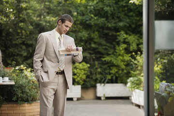 Businessman in garden looking at watch