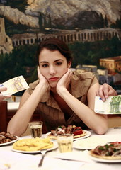 Woman sulking at restaurant table with Euro bills