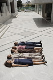 Business people lying on the ground in a row