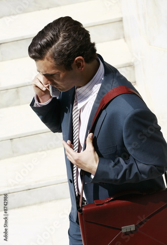 Businessman on the go on cell phone with briefcase