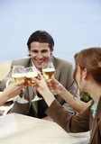 Office workers toasting with beer in outdoor cafe