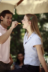 Man feeding woman a potato chip