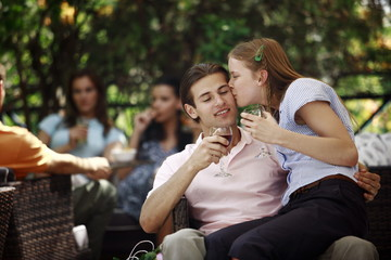 Woman sitting on man's lap in outdoor cafe