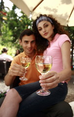 Woman sitting on man's lap holding glasses of wine