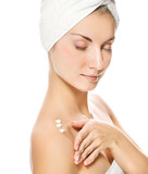 Young lovely lady applying moisturizer to her skin after shower poster