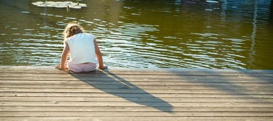Daydreaming: little girl sitting on the water chilling her feet