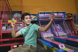 Male teenager with cell phone in arcade