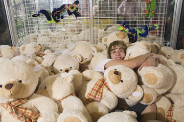 Male teenager among teddy bears in arcade