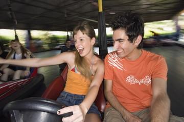 Teenage couple in bumper car in amusement park
