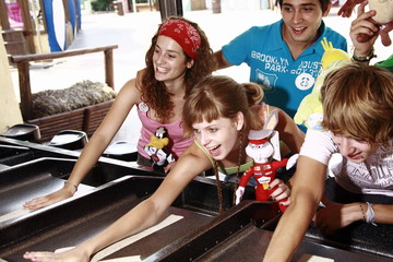 Teenagers playing game in amusement park