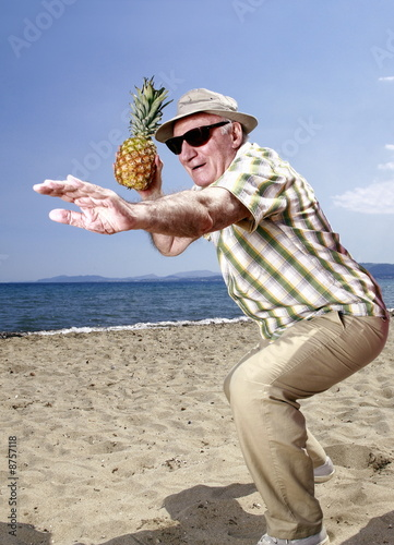 Male senior with pineapple on the beach