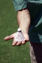 Hand holding badminton ball