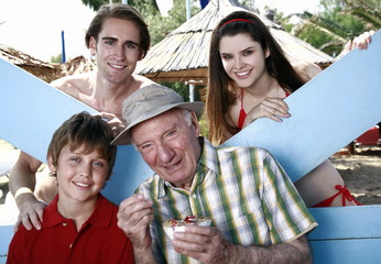 Grandfather;grandson;and young adult couple eating at beach