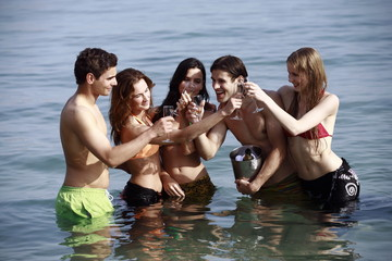 Two male and three female young adults toasting in sea