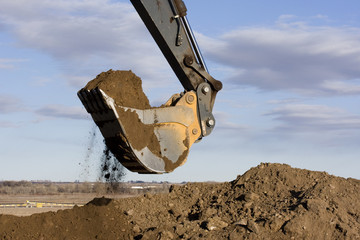 Excavator arm and scoop digging dirt at construction site