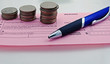 Coins on Deposit Slip with pen