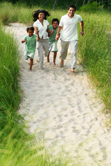 Happy Family Running Together Down a Sand Path