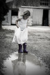 Little Girl in Dress and Wellies in a Puddle