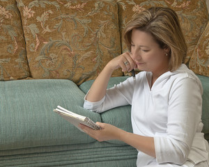 Mature woman holding journal and thinking.