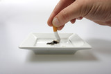 Hand stubbing out a cigarette on white ashtray isolated on white poster