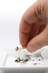 Hand stubbing out a cigarette on white ashtray isolated on white