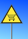 sign with a shopping cart against a blue sky