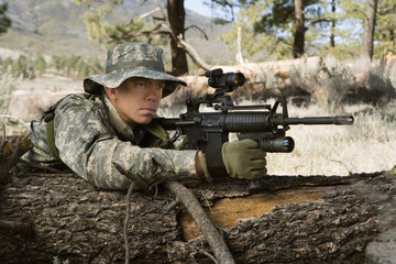 Soldier aiming machine gun, leaning on log