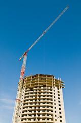 building and crane over blue sky