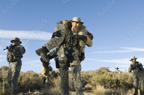 Soldiers walking in field, one carrying colleague