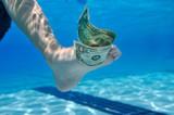 Dollar bill underwater between toes poster