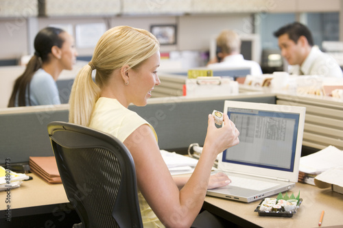 Businesswoman in cubicle using laptop eating sushi