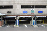 Parking garage entrance with signs and automatic gates. poster