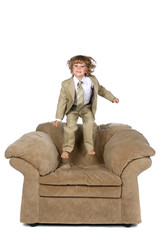 boy in suit jumping on chair