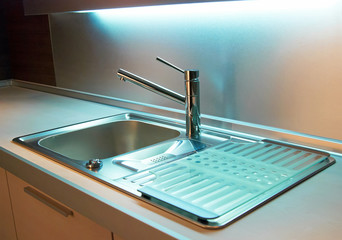 Modern stainless steel tap in white kitchen