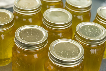 Mason jars filled with clear sweet honey.