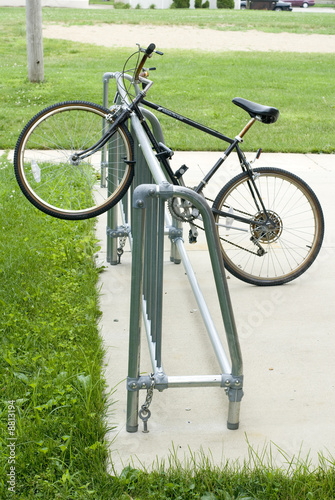 A black mountain bike locked to a public bicycle rack. .