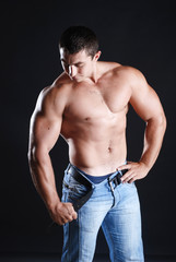 Young man athlete with perfect body at black background