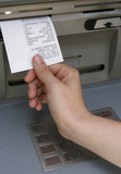 Hand taking a receipt of an Automated Teller Machine poster