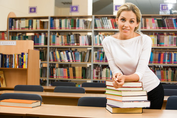 Image of teacher standing near table with books on it