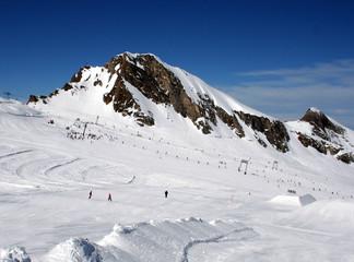 Skiers on mountainside in Swiss Alps scenery.