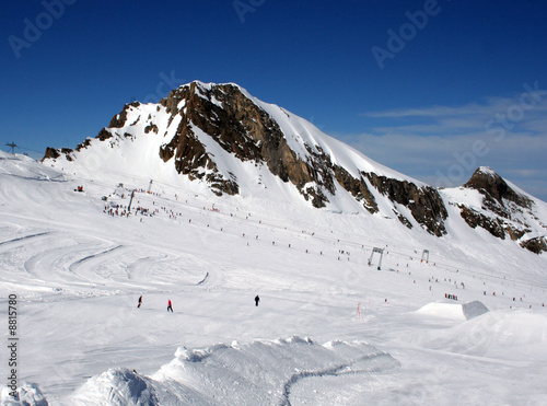 Skiers on mountainside in Swiss Alps scenery.