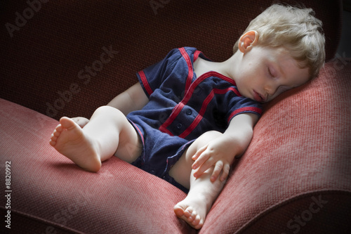 Young tired boy taking a nap on a red sofa