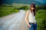 Young lonely teenager girl with wet hair staying on road poster