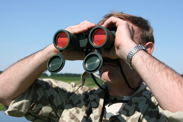 Male field officer watching thru binocular