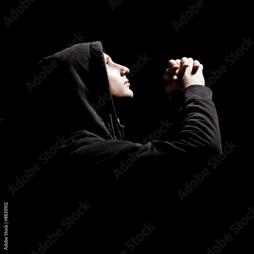 young man is praying against black background