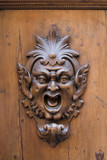 Carved gargoyle adorning a wooden door in Siena, Italy poster
